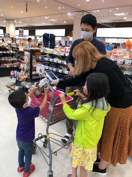 子供と一緒にレジゴーで商品をスキャンする家族